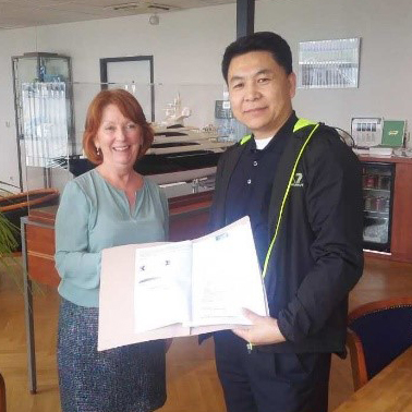 Angie Deady-Fiddler, Director of Martyn Fiddler Aviation handing over the completed customs paperwork to Li Zheng, Executive Vice President of Deer Jet.